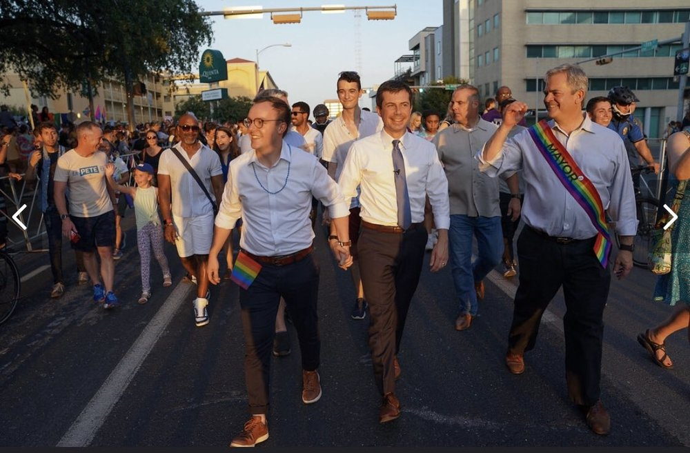 Pete and chasten walk in the Austin Pride Parade
